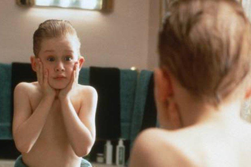 Menino em cena clássica em frente ao espelho
