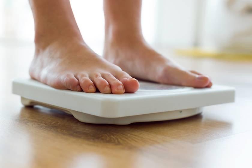 pessoa se pesando em balança