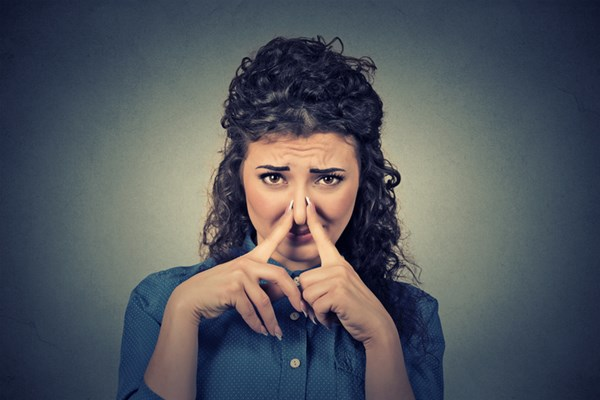 young woman pinches her nose with fingers looks with disgust something stinks
