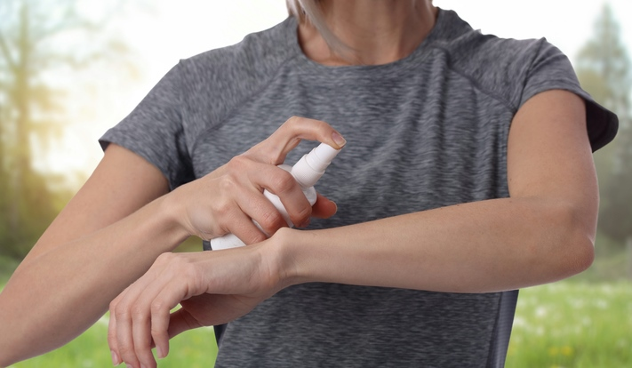 Woman spraying insect repellent
