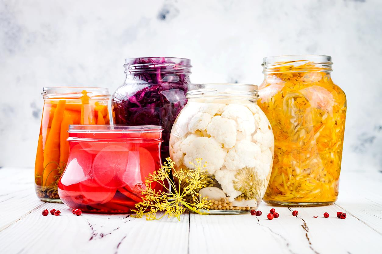 Sauerkraut variety preserving jars. Homemade red cabbage beetroot kraut, turmeric yellow kraut, marinated cauliflower, carrots and radish pickles. Fermented food.