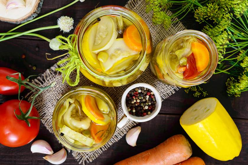 Pickles: vegetable assortment (zucchini, pepper, carrots, tomato, green peas) in glass jars on a dark wooden background. The top view