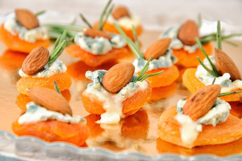 Cocktail snack from dried apricots with gorgonzola and almonds