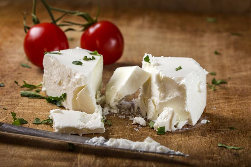 Feta cheese with knife and two cherry tomatoes in background on wood
