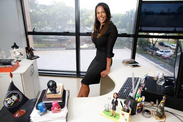 Cynthiane Maria da Silva Santos na sala onde trabalha
