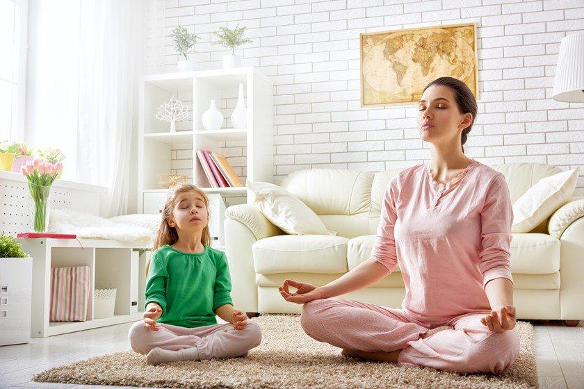 Mulher fazendo yoga com sua filha