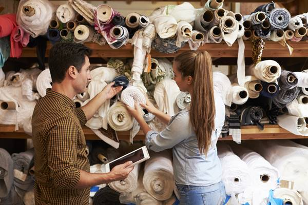 Man and woman selecting fabric from storage shelves