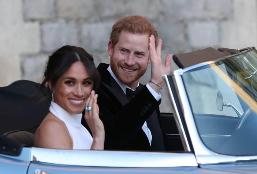 Prince Harry e Meghan Markle acenam para fãs