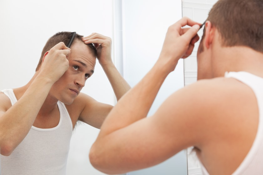 USA, Illinois, Metamora, Man combing hair in front of mirror