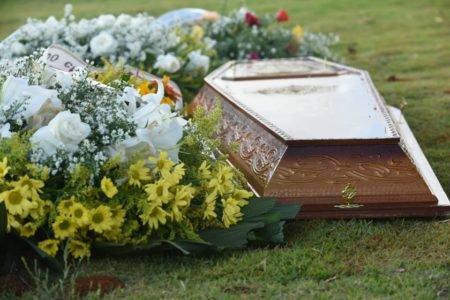 Coroa de flores e caixão em cemitério