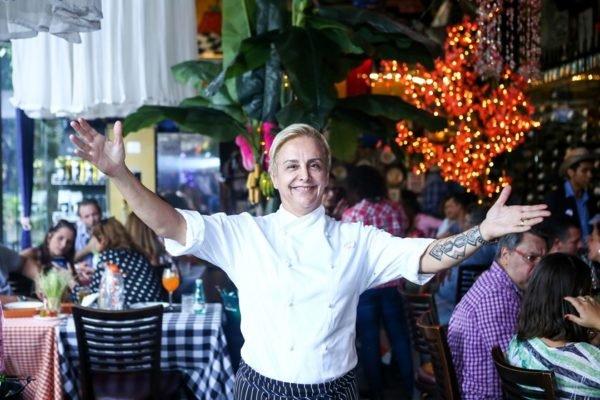 Chef Mara Alcamim e braços abertos em frente a mesas de clientes no Restaurante Universal