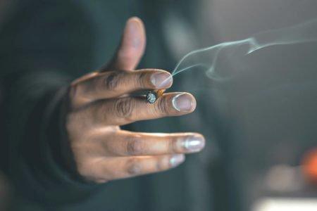 mão segurando cigarro aceso