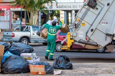 Trabalhador recolhendo lixo ao caminhão