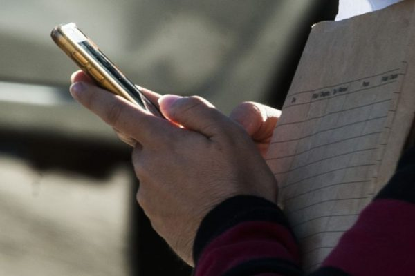Mão mexendo em celular