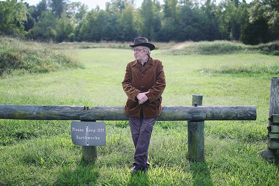 O ex-astrólogo Olavo de Carvalho em pé, encostado em uma pequena cerca