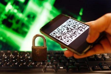 celular com qr code e cadeado sobre teclado