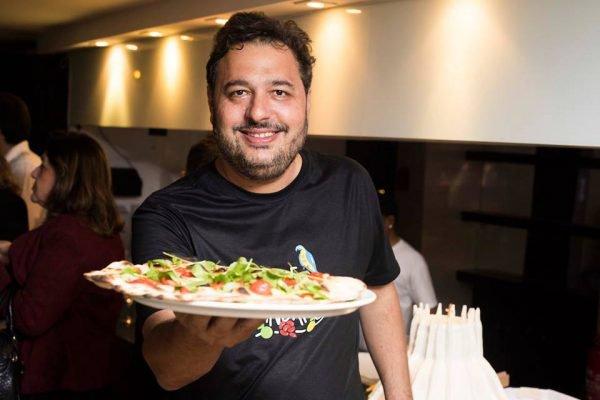 Chef Gil Guimarães segurando uma pizza
