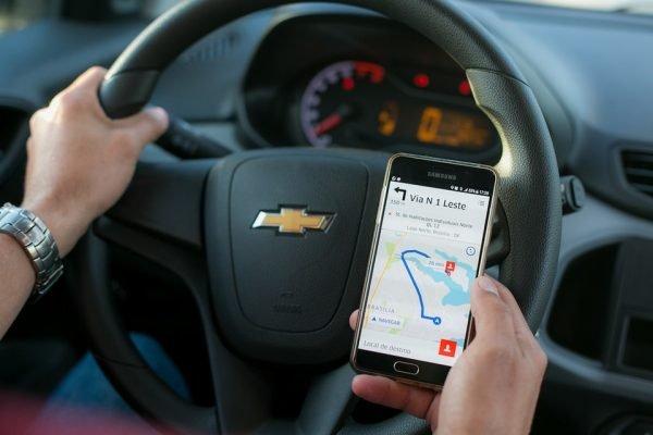 Motorista com a mão no volante e outra com o celular na mão