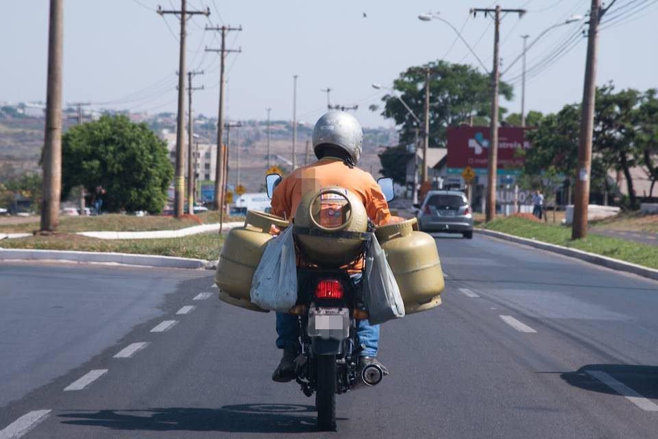 Motociclista levando botijões