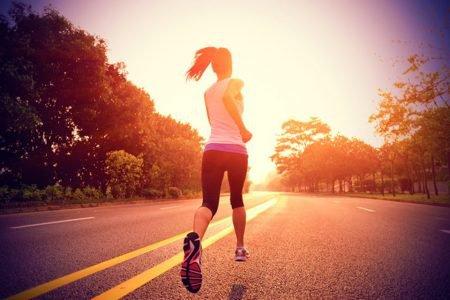 Mulher correndo em rua asfaltada