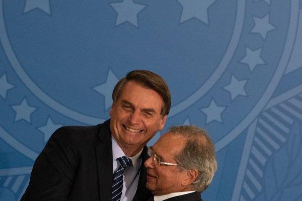 Jair Bolsonaro e Paulo Guedes se abraçam sorrindo