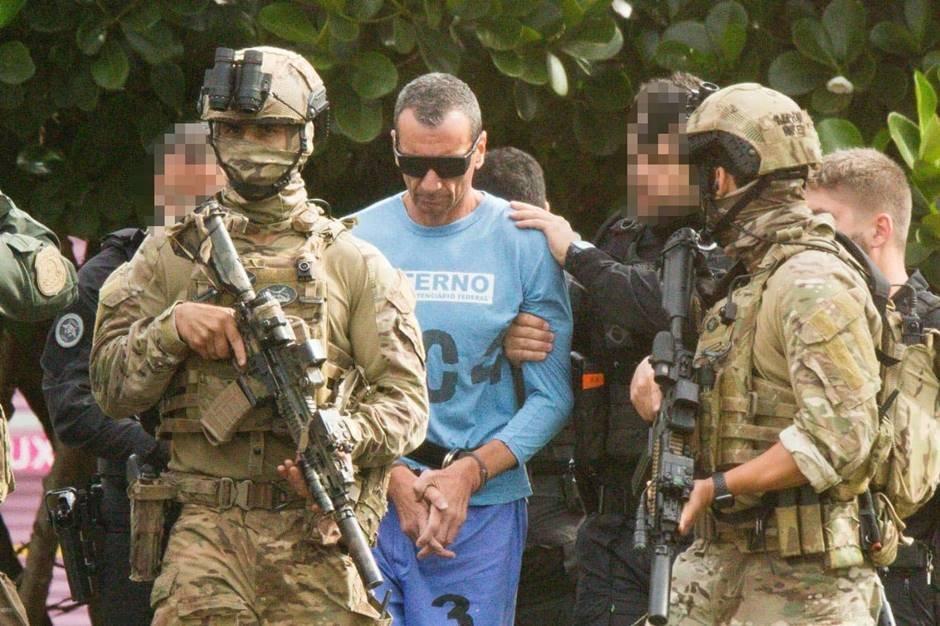 Ao lado de policiais armados com fuzis, Marcola, de camisa azul usa algemas durante escolta