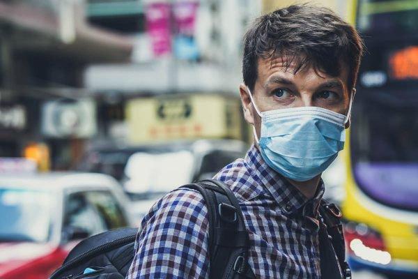 homem de máscara em ponto de ônibus
