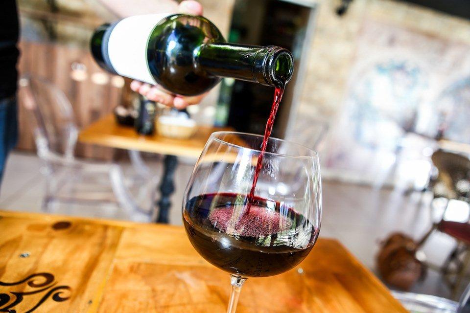 Um vinho tinto é colocado da garrafa para a taça