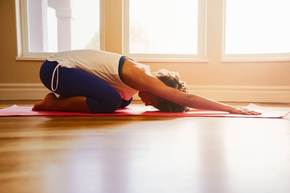 Mulher fazendo yoga na sala de casa