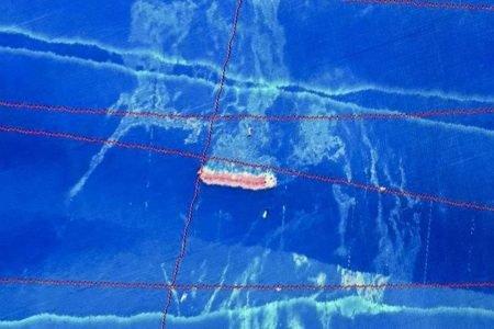 Na imagem, as manchas mais claras, esmaecidas, são o óleo que cerca a embarcação.