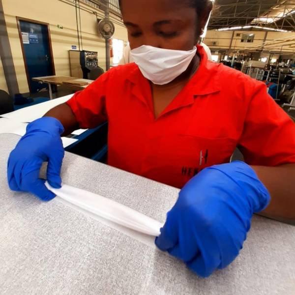 funcionária em fábrica produzindo máscara