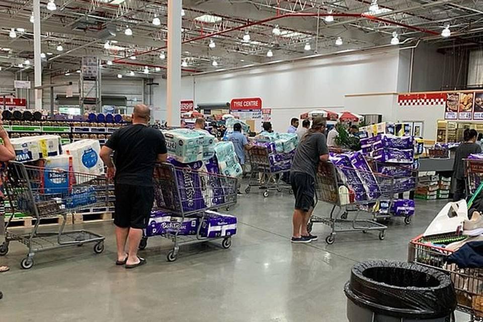 Pessoas com carrinhos de compra em supermercado