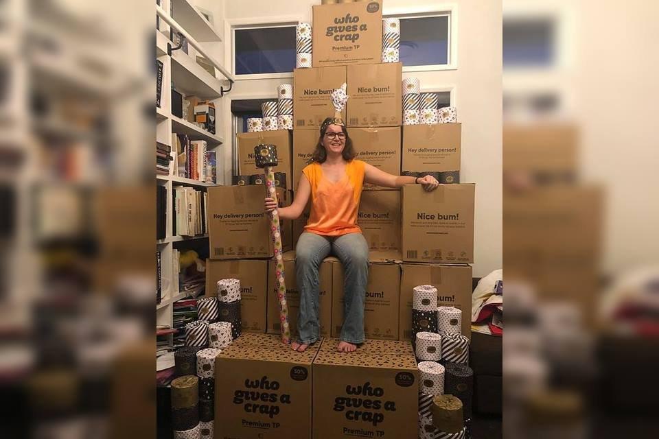 Mulher sentada em caixas de papel higiênico