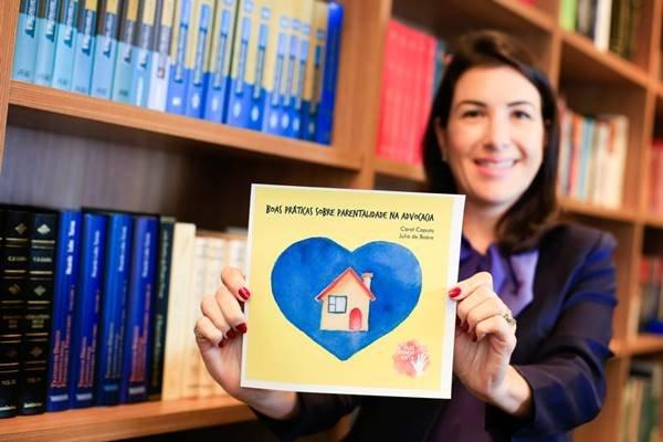 """Advogada Júlia de Baére segura a cartilha """"Boas Práticas Sobre Parentalidade na Advogacia"""""""