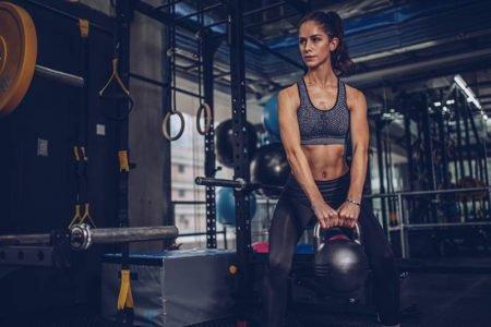 Jovem mulher faz exercício usando kettlebell