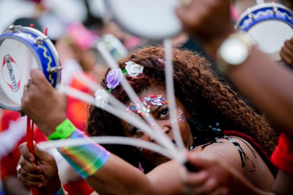 Mulher toca instrumento no Bloco do Galo Cego