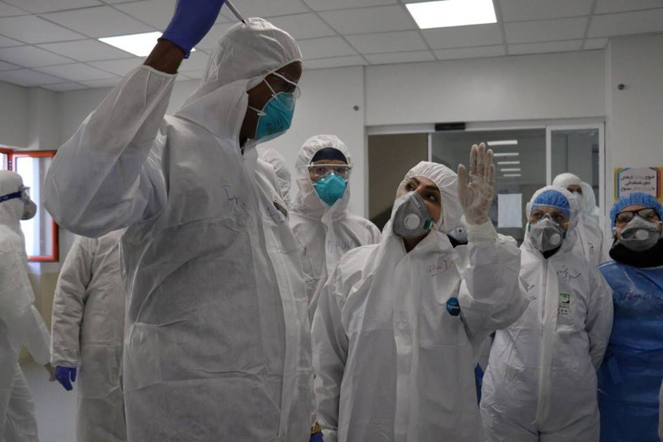 Pessoas com roupas de proteção e máscaras
