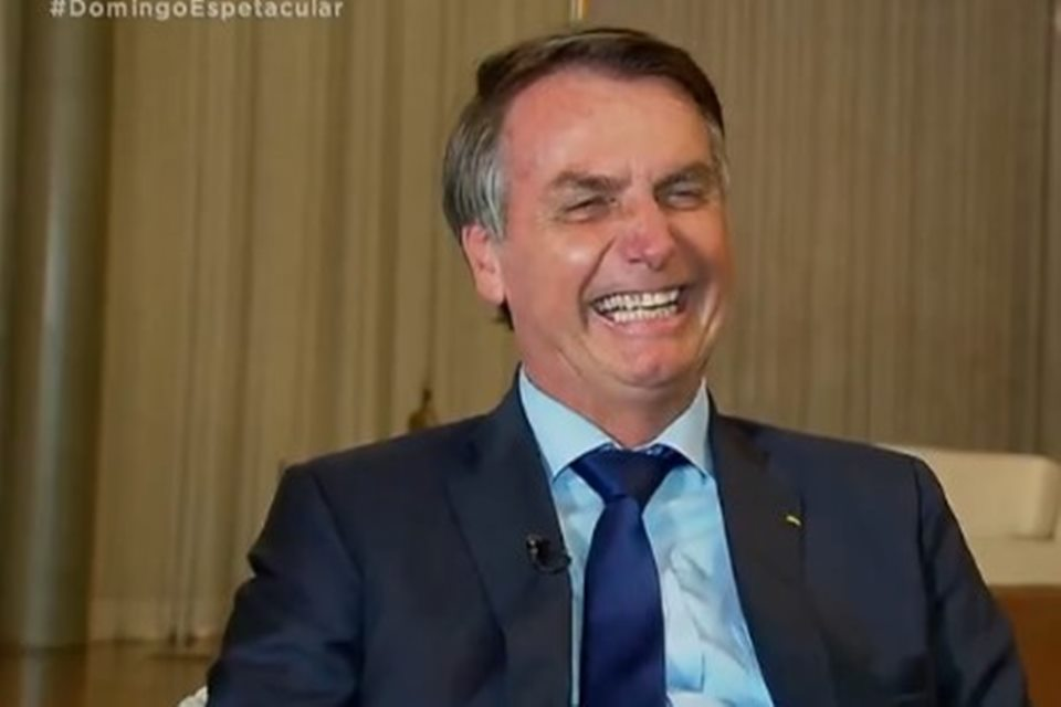 O presidente Jair Bolsonaro sorri em entrevista com comediante