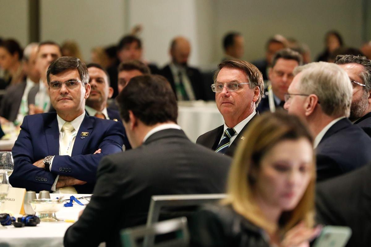 Bolsonaro de óculos sentado em mesa com comitiva nos EUA