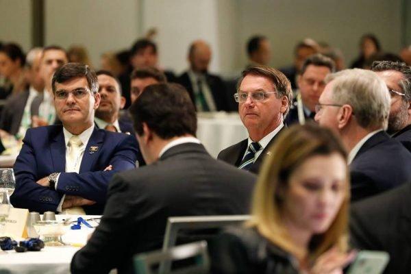 Bolsonaro sentado em mesa com outros homens em evento nos EUA