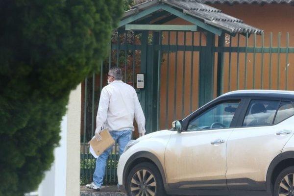 Oficial de Justiça, com máscara, tenta falar com marido de paciente que tem coronavírus