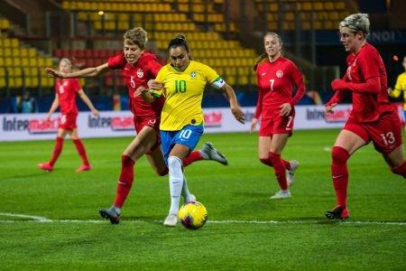 Marta protege a bola entre as marcadoras do Canadá