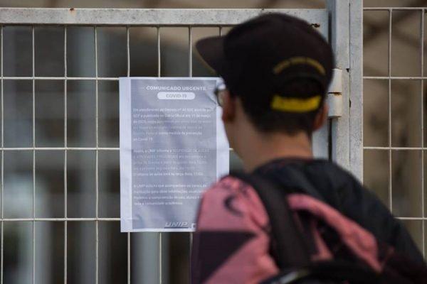O estudante Marcos Barbosa lê aviso em frente à Unip avisando suspensão de aulas por causa do novo coronavírus