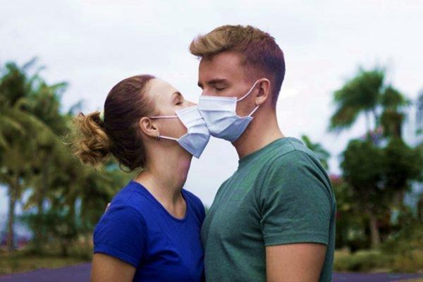 Homem e mulher se beijam usando máscaras de prevenção ao coronavirus