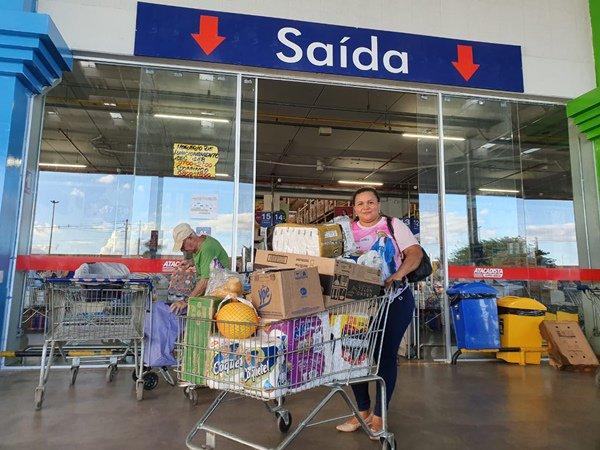 Consumidora saindo de supermercado com carrinho cheio