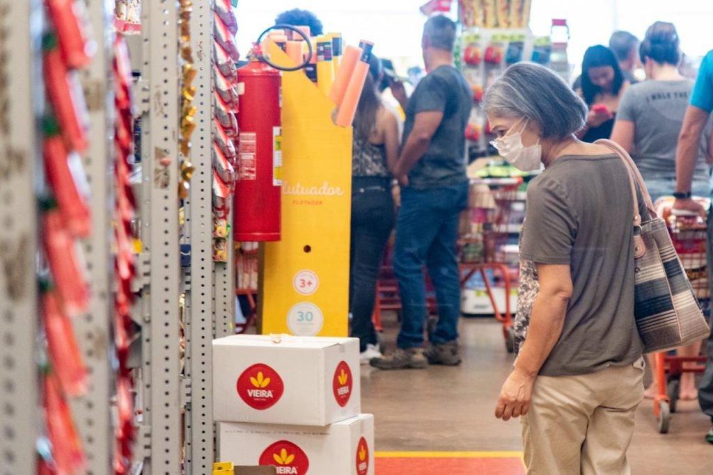 Mulher usa máscara para fazer compras em supermercado