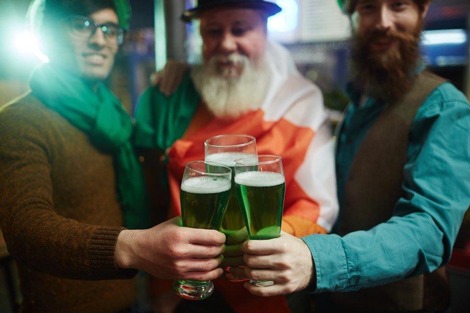 Homens brindando com chope verde