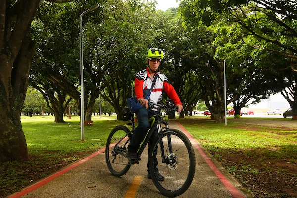 Homem com bicicleta em ciclovia