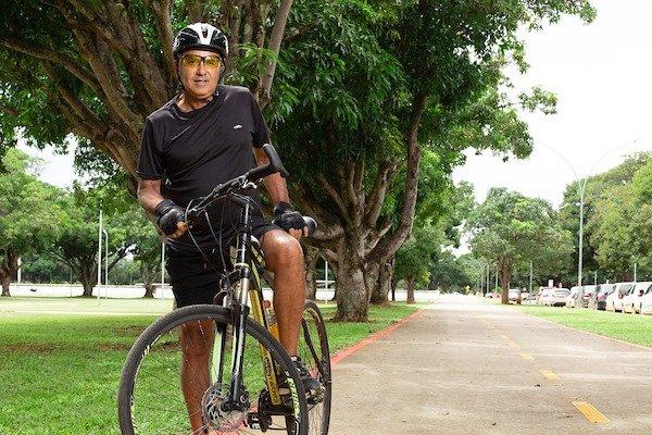 Homem em bicicleta em ciclovia