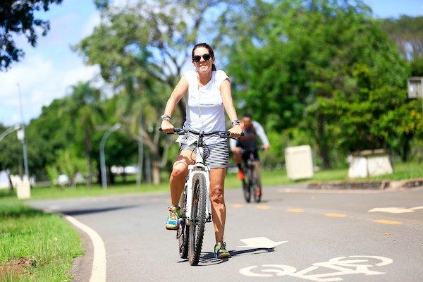 Mulher anda de bicicleta em ciclovia do Parque da Cidade